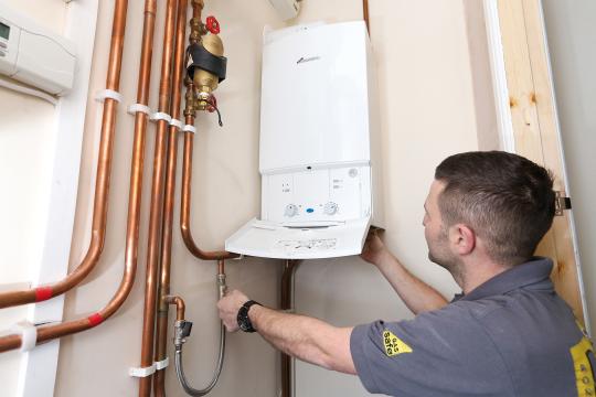 Gas engineer inspecting boiler